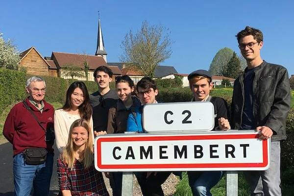 Students on an excursion behind the sign to Camembert