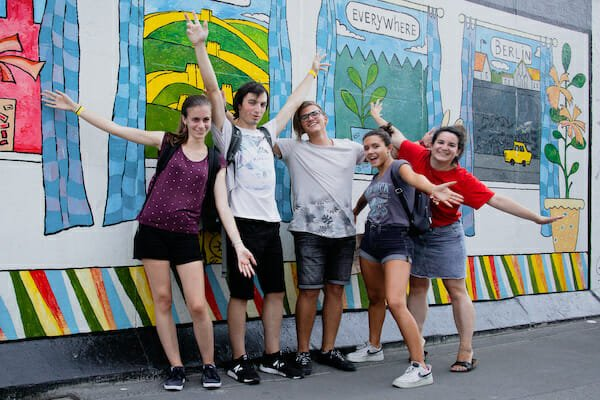 Students on a walking tour of Berlin in front of graffiti wall