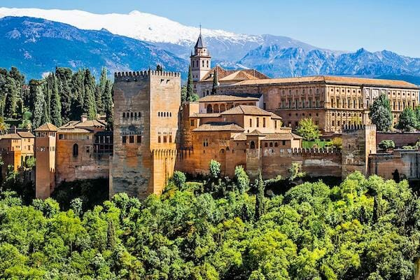 The Alhambra with the Sierra Nevada mountains behind covered in snow.